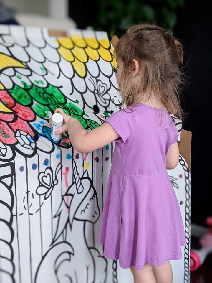little girl coloring on and painting a cardboard colorable playhouse
