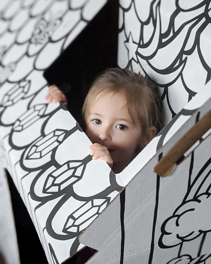little girl peeking out of a box