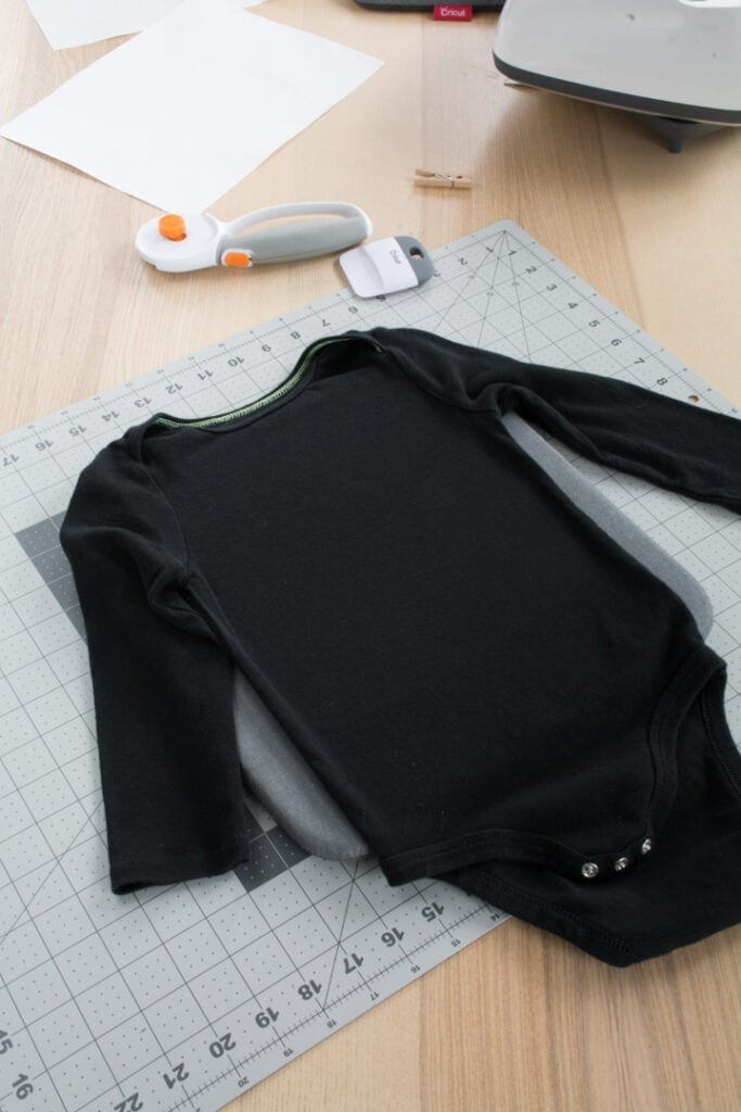 black baby bodysuit on a table