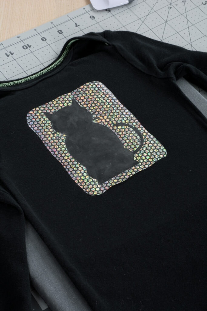 Cricut Holographic Mosaic Iron On cut in a cat shape on a black baby bodysuit
