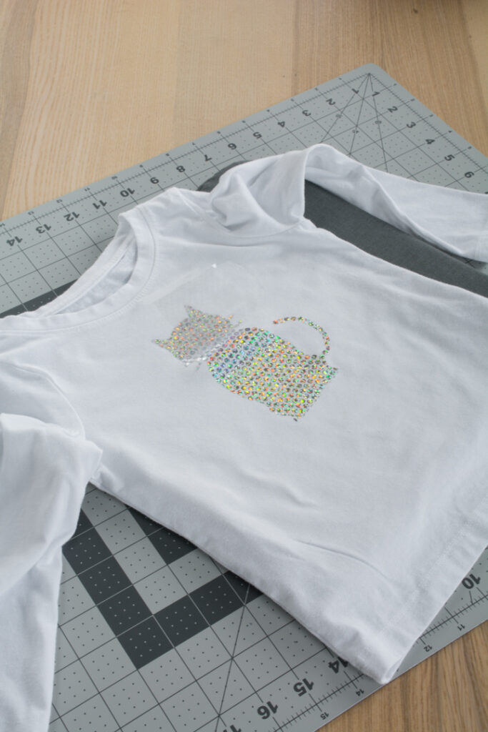transferring Cricut Holographic Mosaic Iron On  in a cat shape to a white shirt
