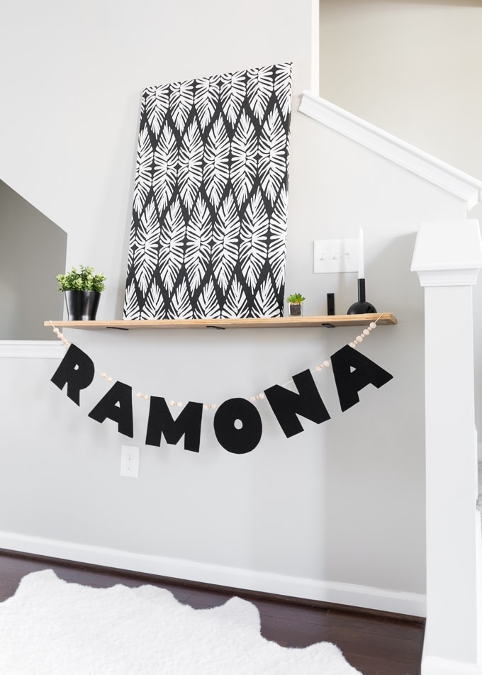 No-Sew Felt Name Garland with wood beads hanging on a shelf