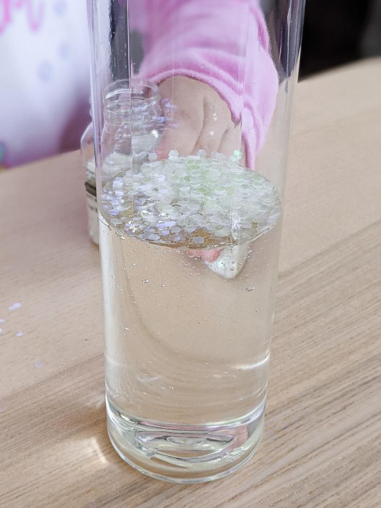 adding glitter to the DIY glitter sensory bottle