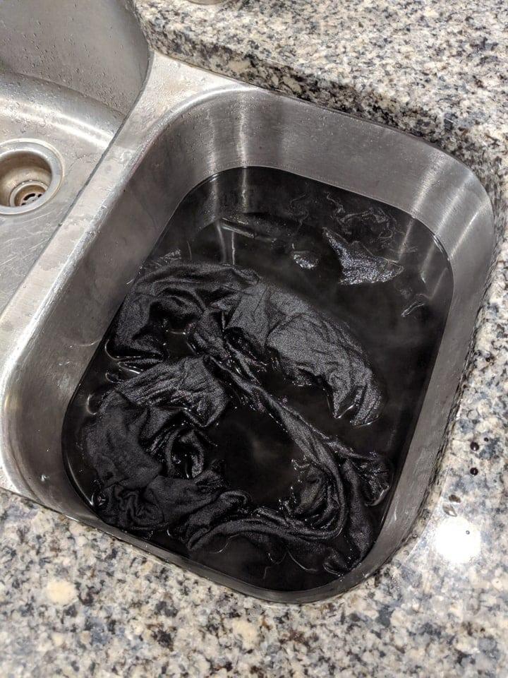 adding the dress to the black dye bath