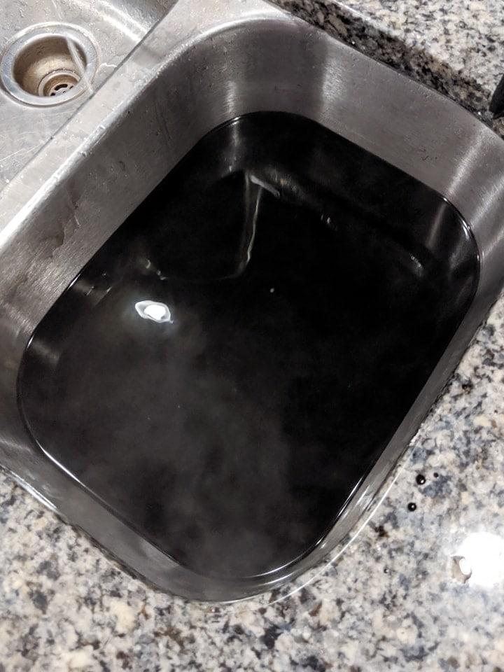 black dye bath in a sink