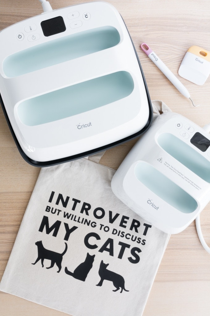 tote bag with a design on it saying introvert but willing to discuss my cats and two Cricut Easypresses