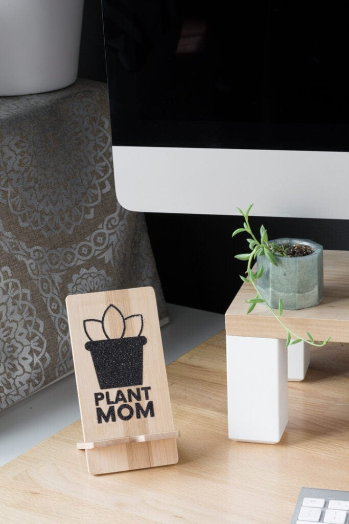 using the Cricut EasyPress mini to transfer a black glitter iron-on design to wood