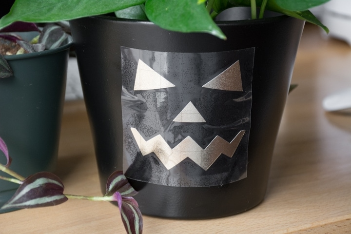 jack-o-lantern faces cut out on vinyl and transferred onto a planter pot