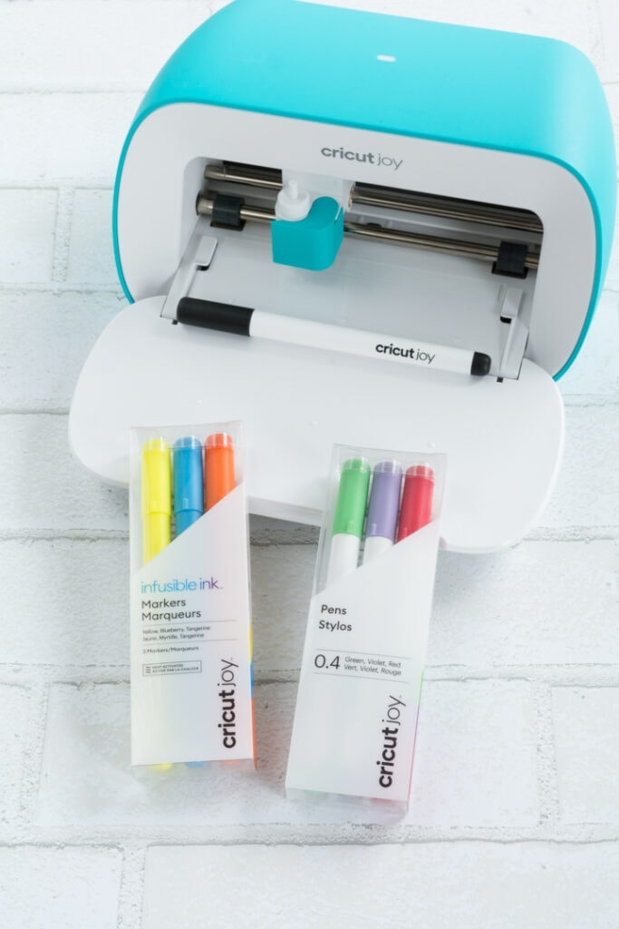 Cricut joy machine and pens in packages