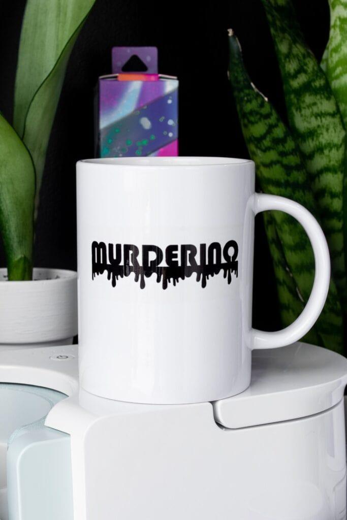 mug that says murderino sitting on top of a Cricut mug press
