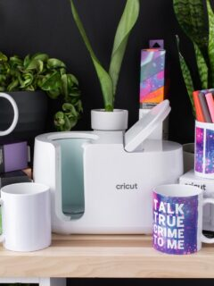 Cricut mug press on a table with mugs and plants
