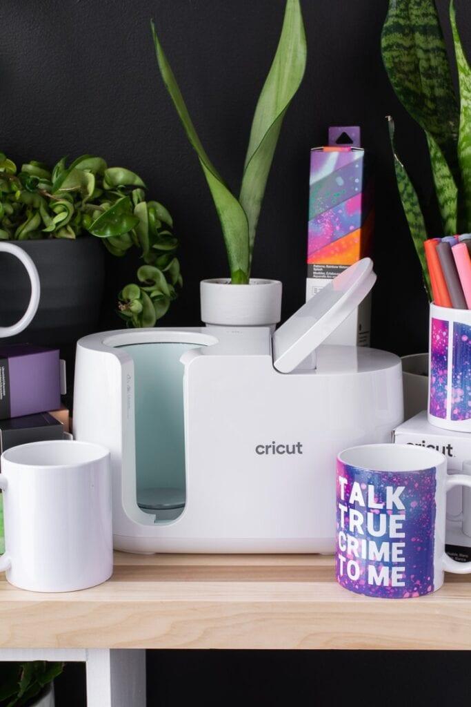 Cricut mug press, mugs, Infusible Ink transfer pens, infusible ink transfer sheets, and plants on a table