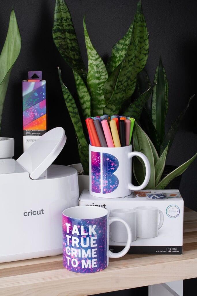 Cricut mug press, mugs, Infusible Ink transfer pens, and plants on a table