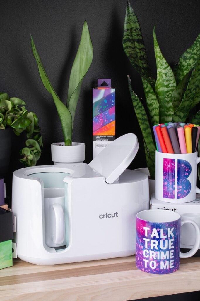 Cricut mug press, mugs, Infusible Ink transfer sheets, and plants on a table