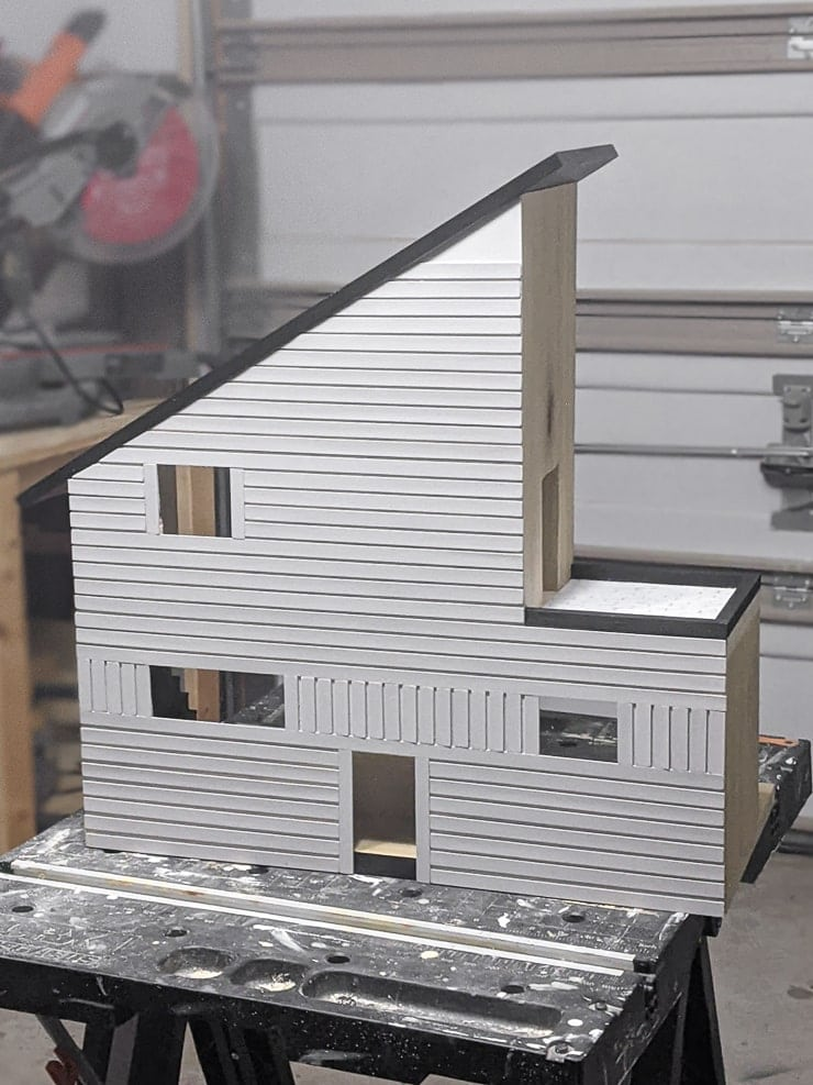 adding painted pieces of balsa wood to the dollhouse using wood glue and painter's tape