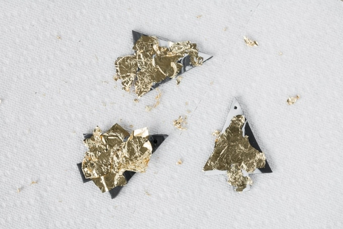 adding gold leaf to the marbled clay Christmas ornaments
