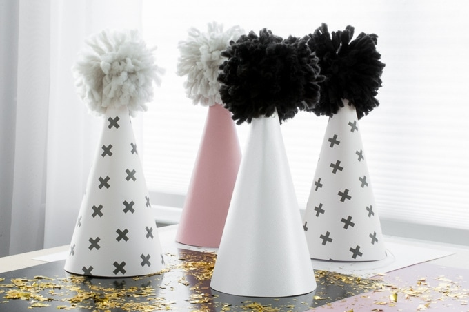 finished scrapbook paper and yarn pom pom party hats