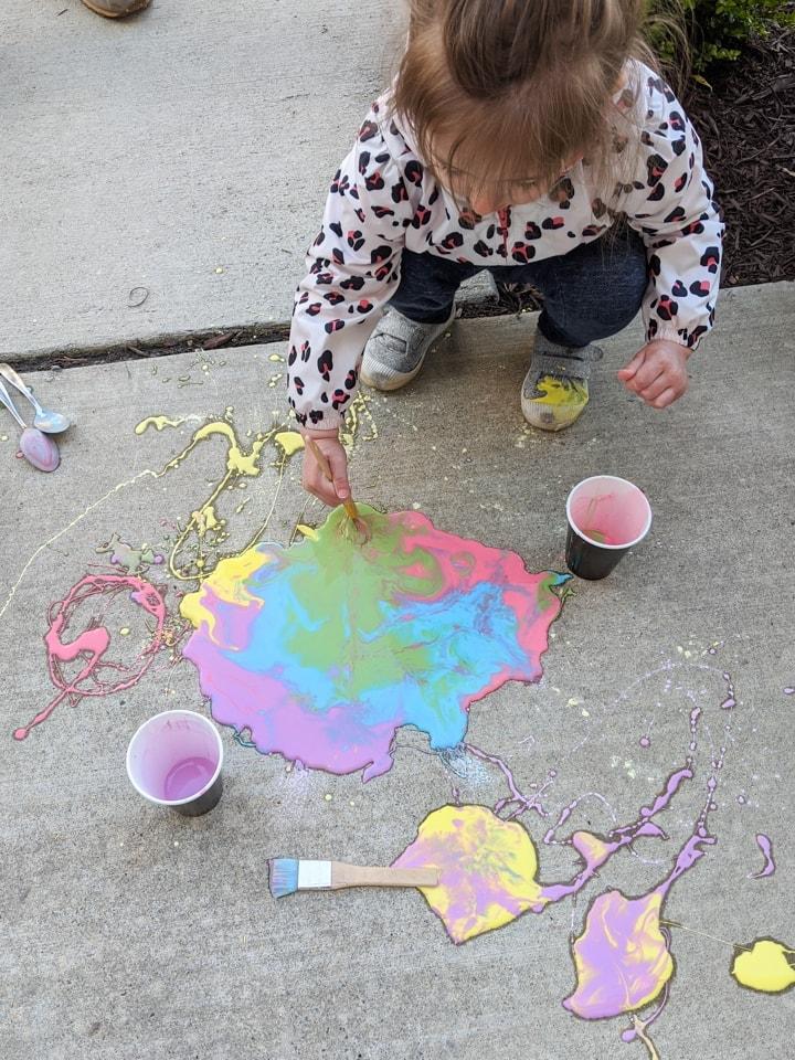 painting on a sidewalk using DIY sidewalk chalk paint
