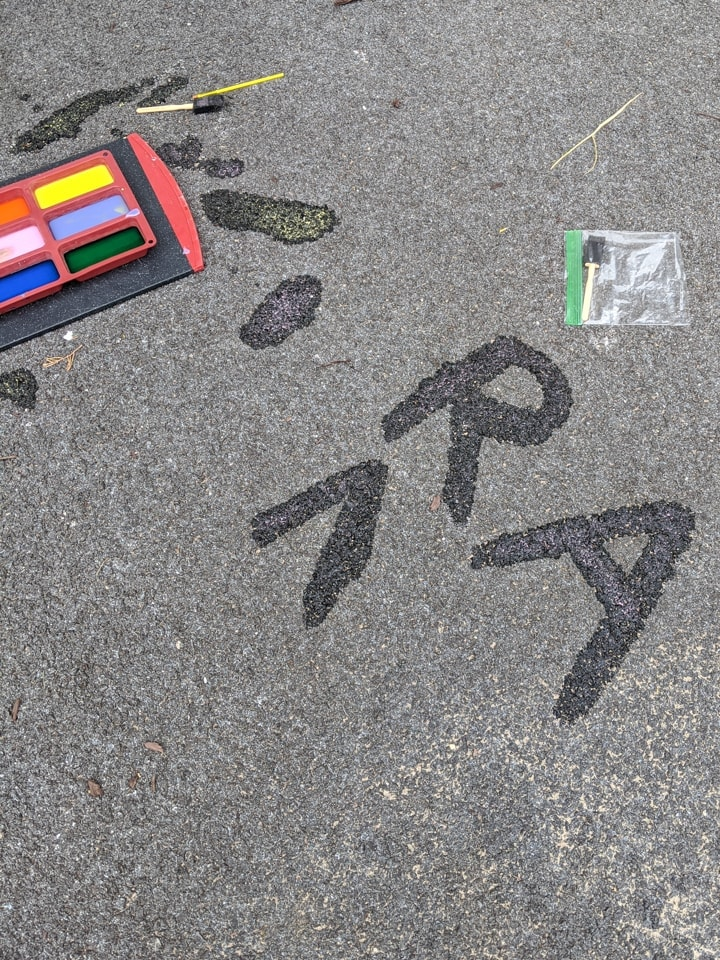 painting DIY sidewalk chalk paint using a paint brush