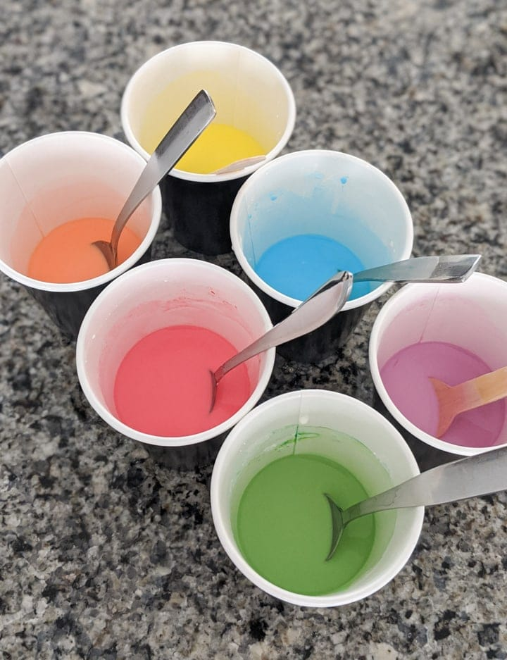 adding food coloring mix to corn starch and water mixtures