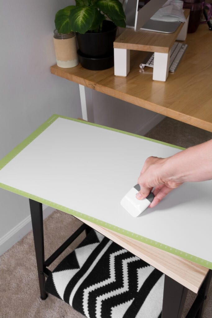 using a scraper to push out air bubbles after adhering vinyl to a standard mat