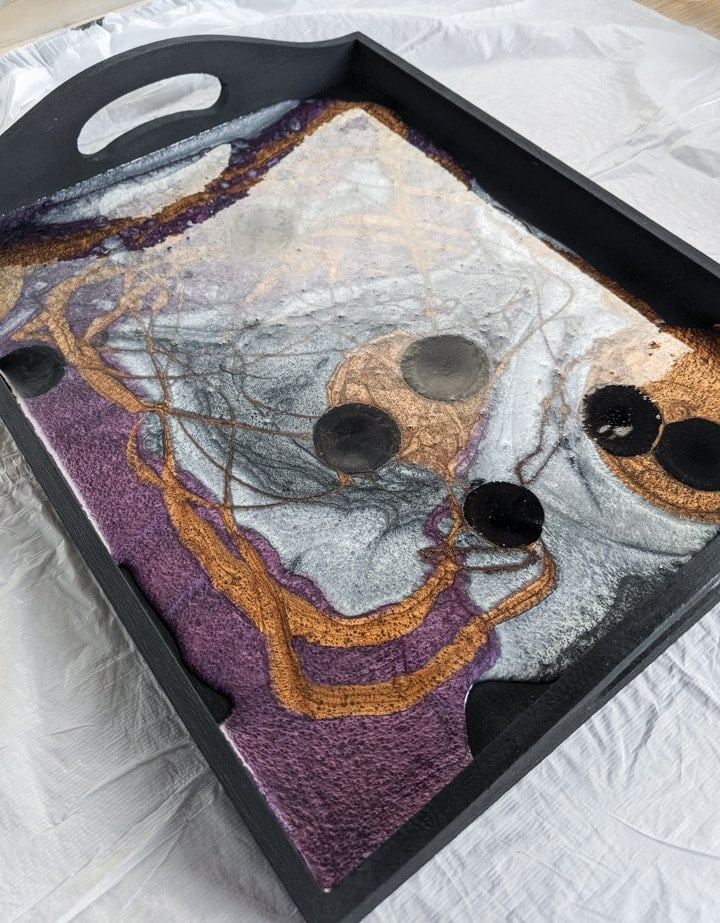pouring colored resin into a painted tray