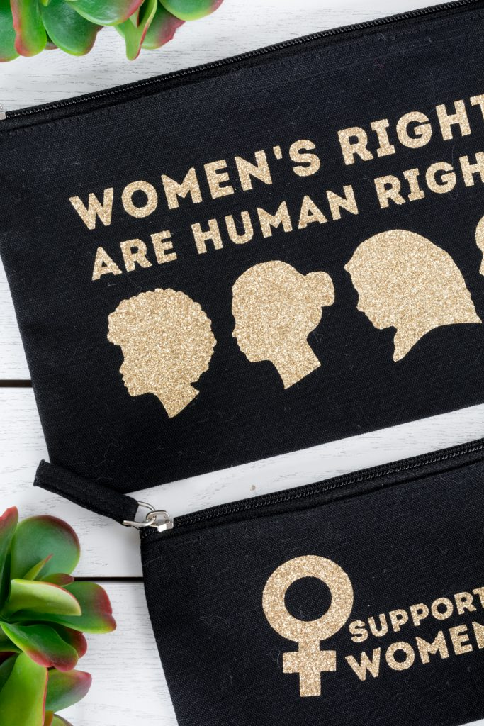 """zippered pouches with """"women's rights are human rights"""" and """"support women"""" decals on them"""