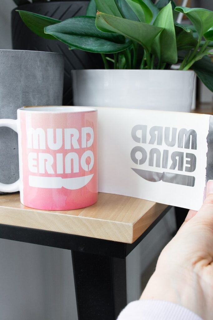 """removing an Infusible Ink transfer sheet from a mug that says """"murderino"""" created with a Cricut Mug Press"""