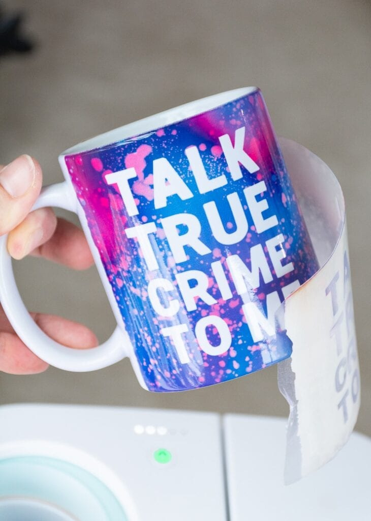 """removing an Infusible Ink transfer sheet from a mug that says """"talk true crime to me"""" created with a Cricut Mug Press"""