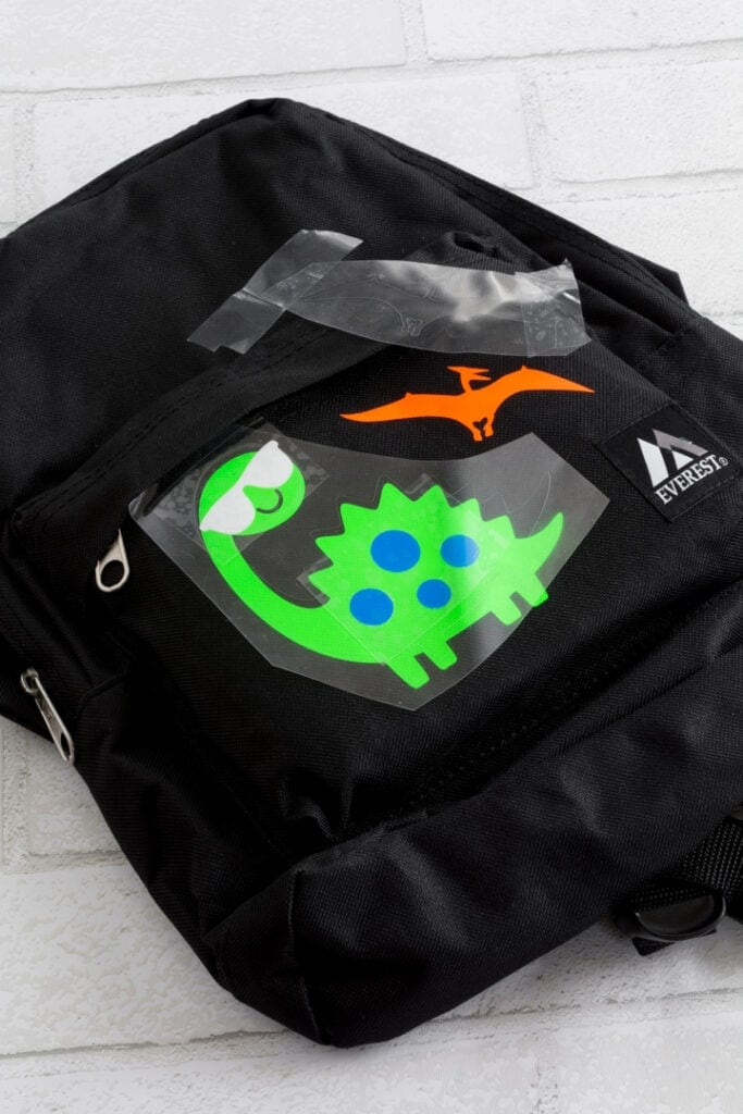 transferring dinosaurs cut out of vinyl to the backpack