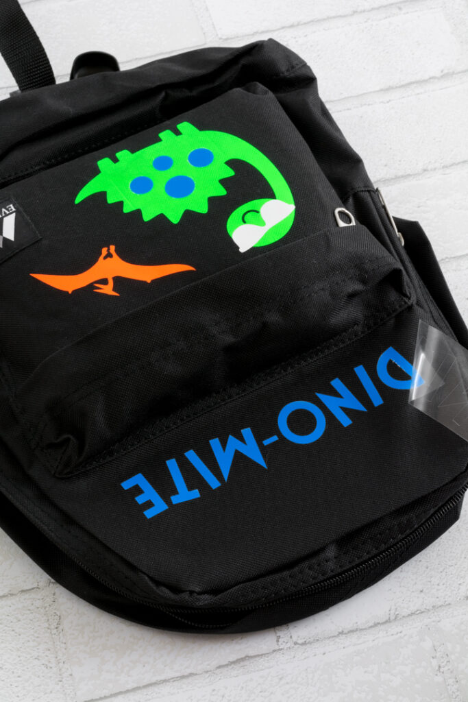 """transferring the word """"dino-mite"""" to the backpack using iron-on"""