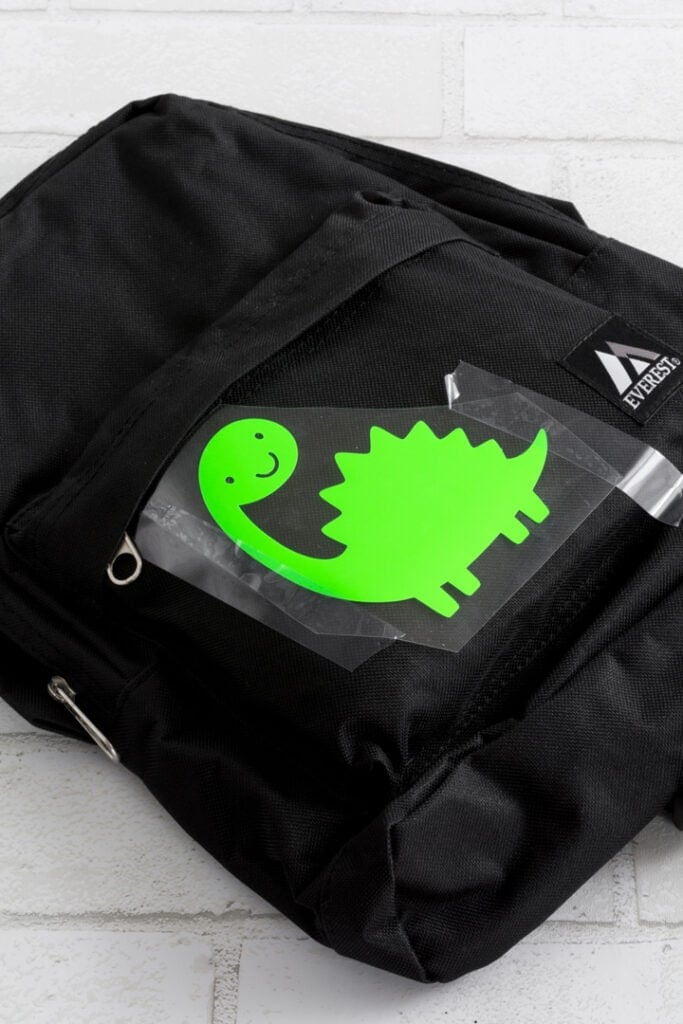 transferring a dinosaur cut out of vinyl to the backpack