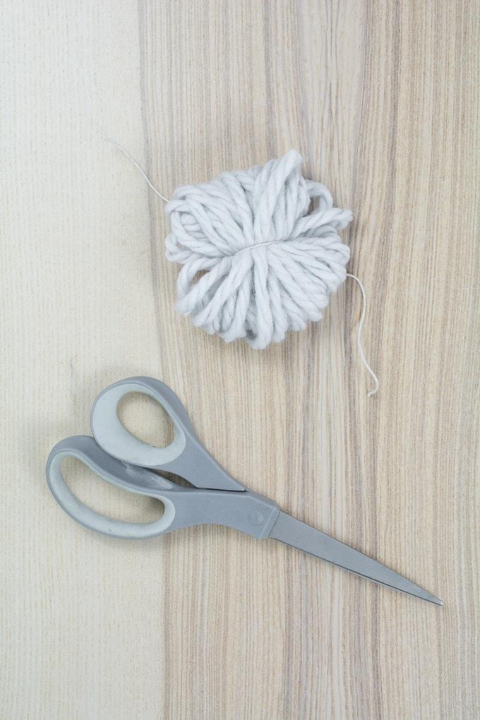 tying twine around the yarn to make a pom pom