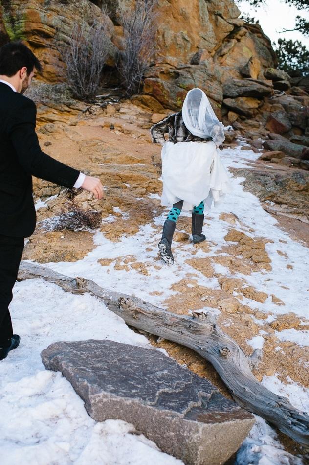 woman in a wedding dress walking up a snowy mountain