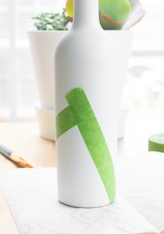 putting painter's tape on a painted wine bottle