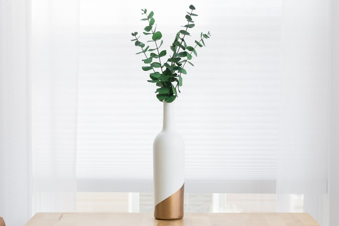 finished wine bottle bud vase with dried eucalyptus in it