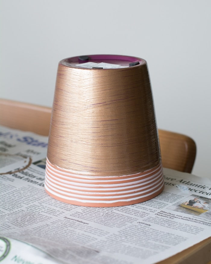painting a clay pot using acrylic paint