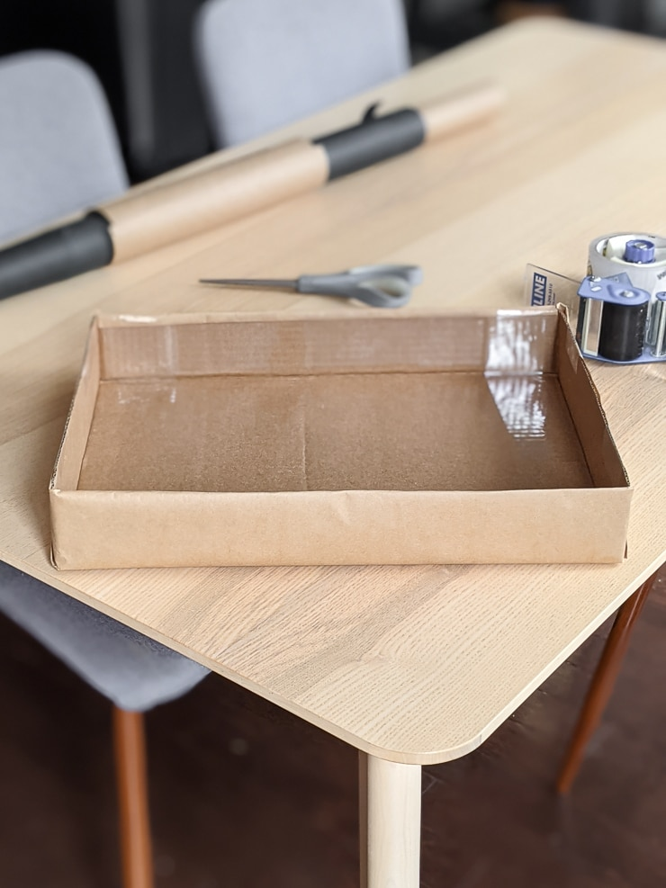 cardboard box with the top cut off on a table