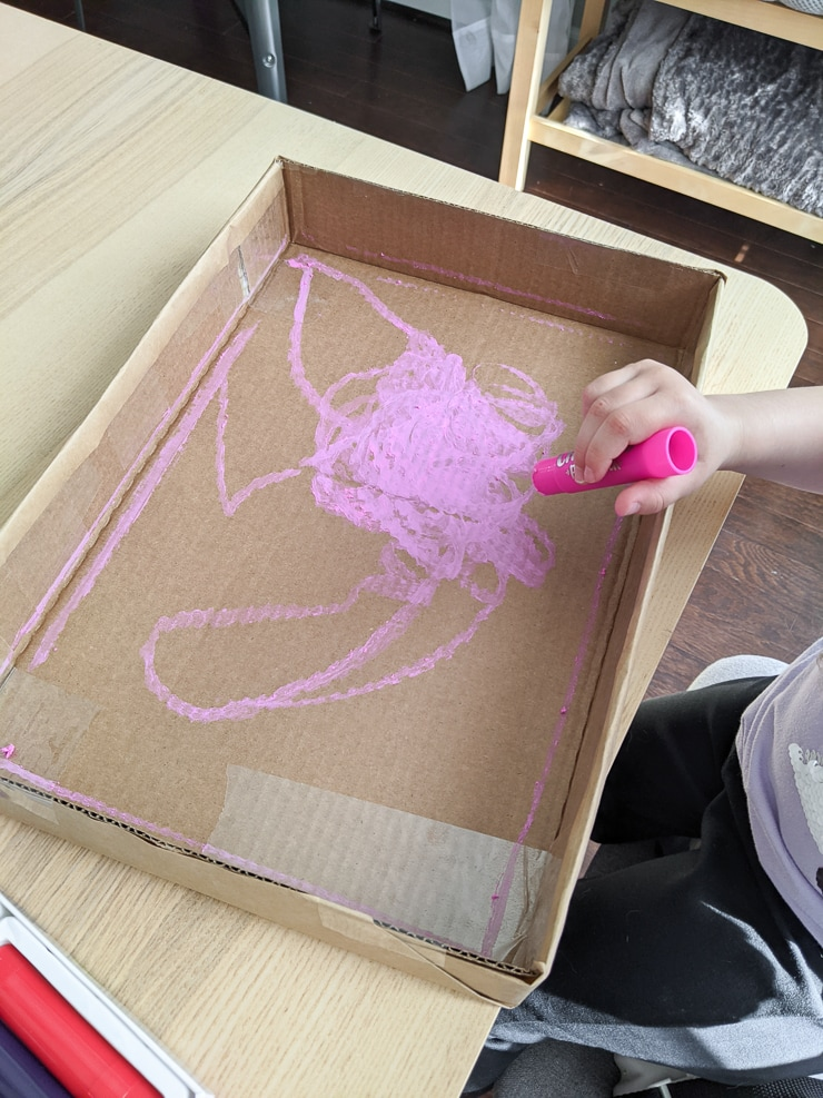 toddler painting a cardboard box