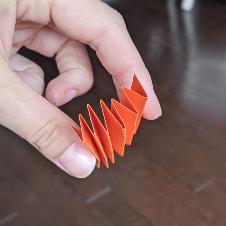 folding a piece of orange paper