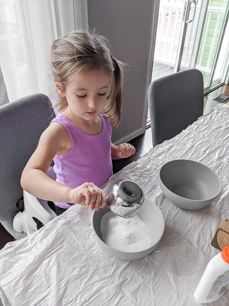 toddler mixing ingredients for DIY slime
