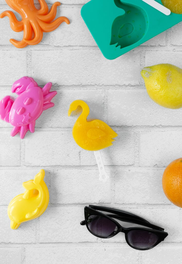 homemade orange juice popsicle made in a flamingo mold