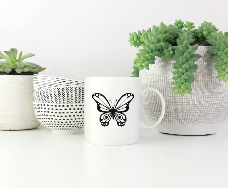 free Cricut butterfly SVG file mocked up on a coffee cup