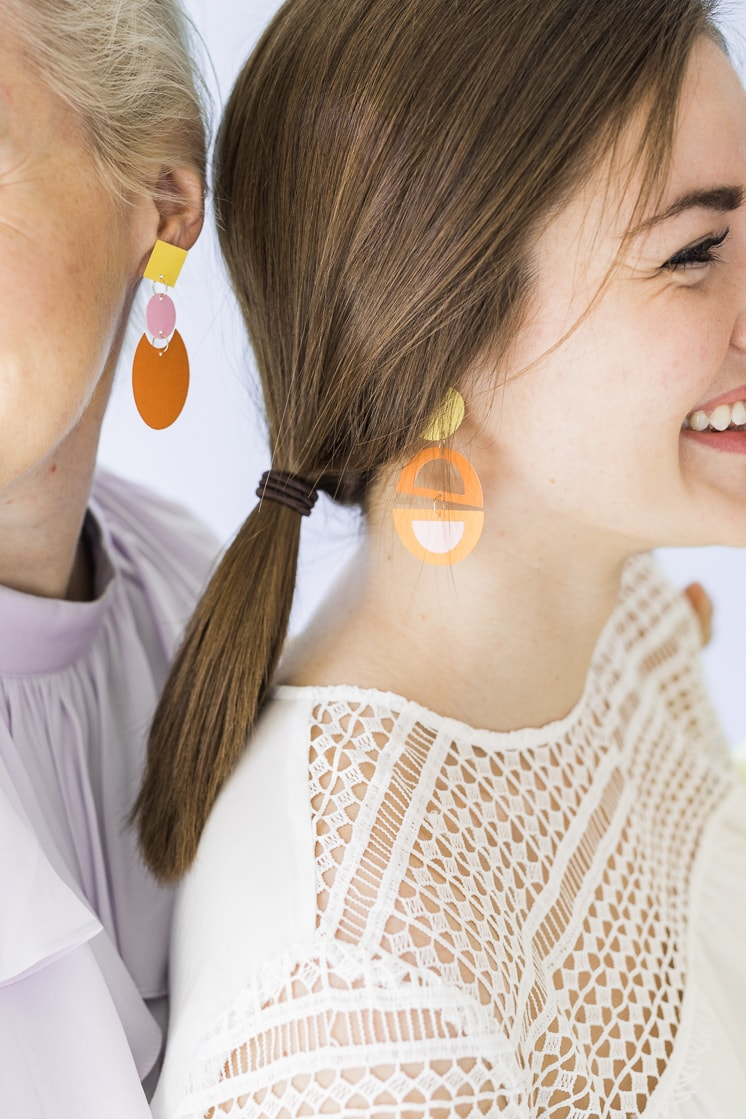 women wearing colorful paper earrings made with Cricut