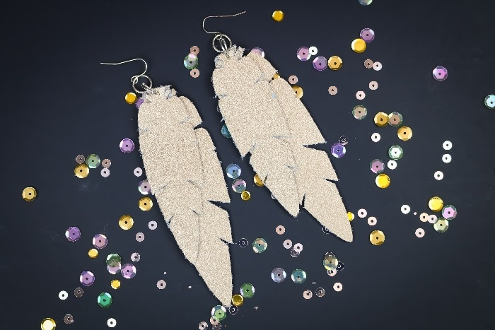 double feather earrings laying in sequins