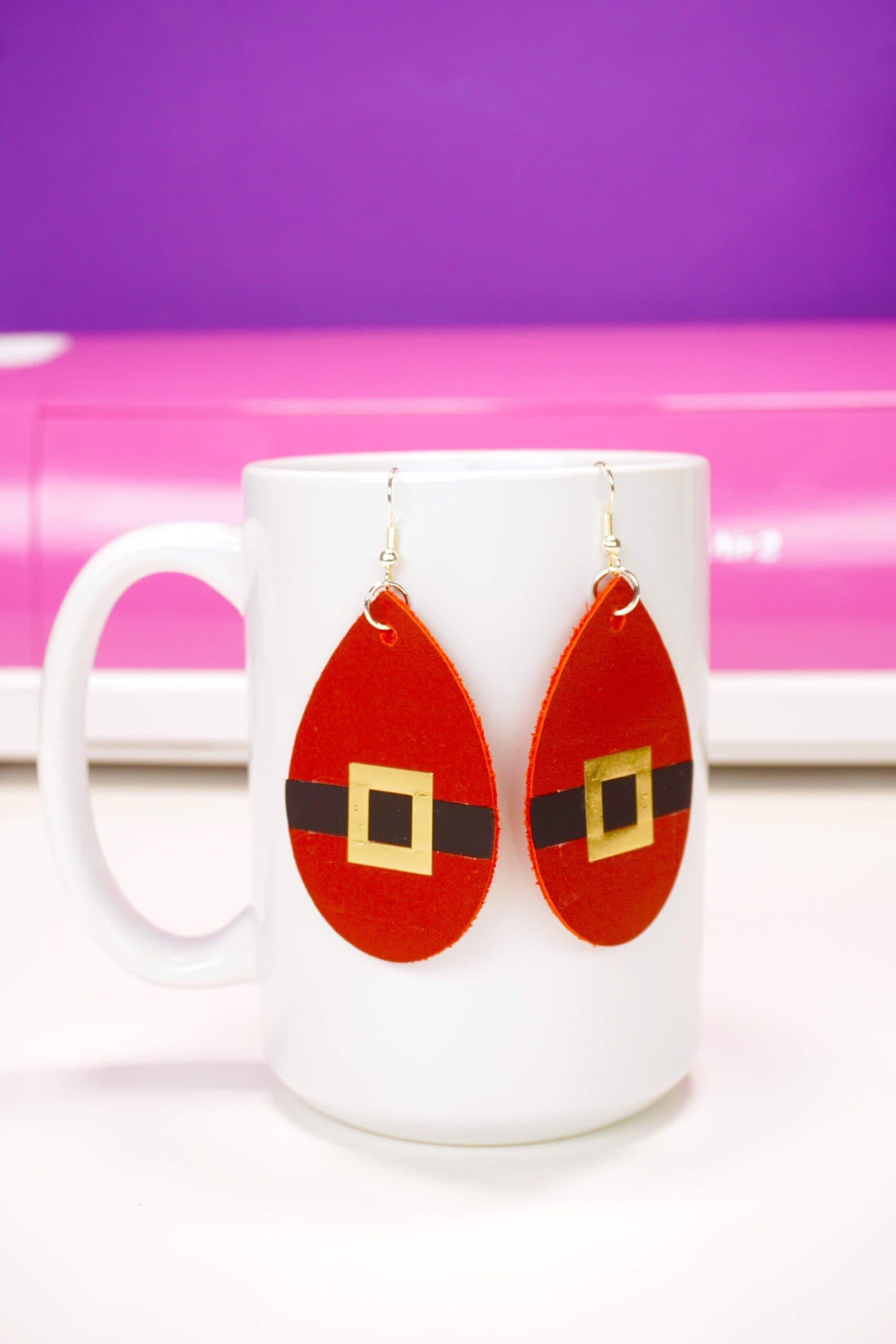 santa suit earrings hanging on white mug