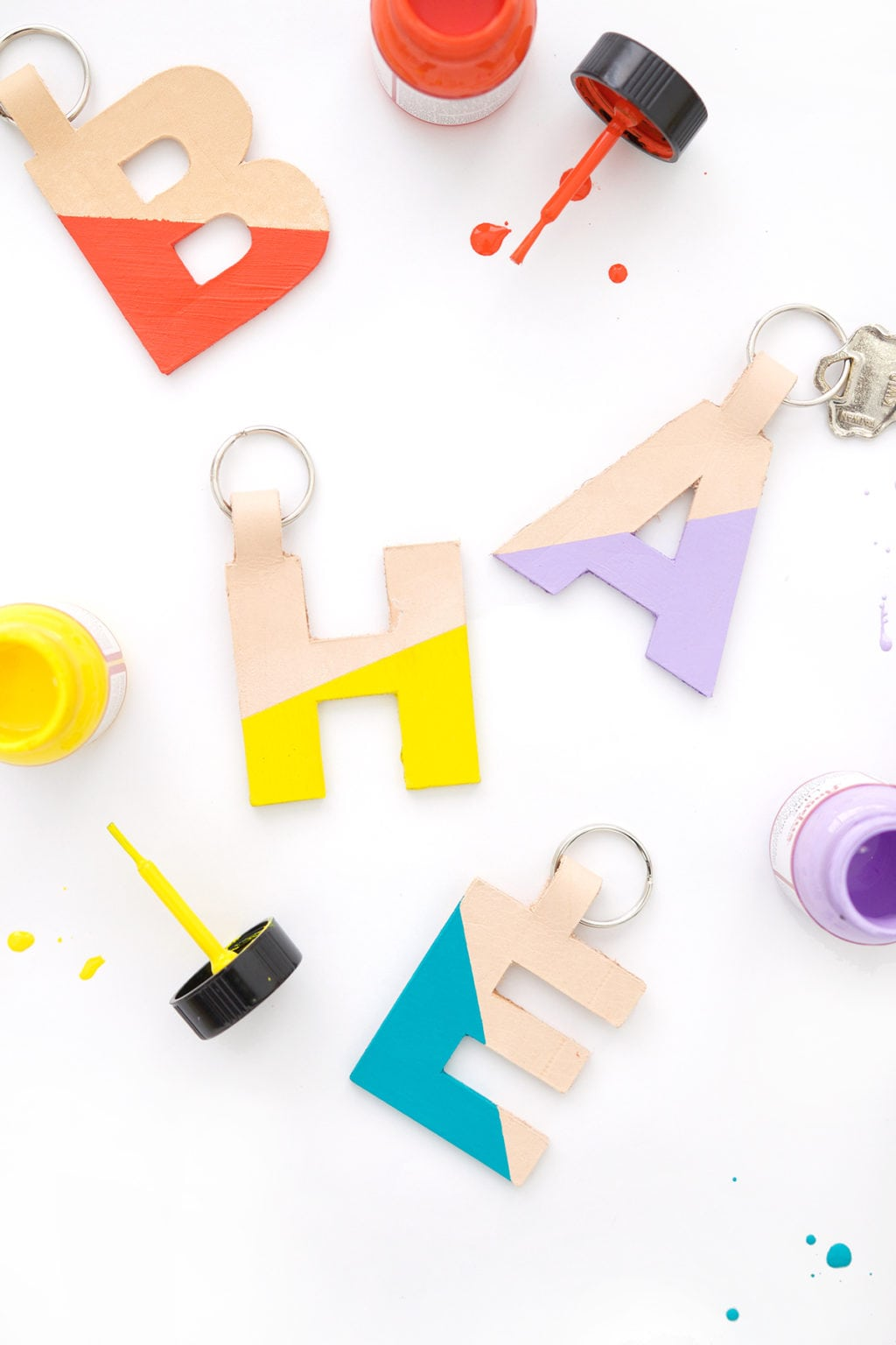 monogram keyrings made from leather painted in color blocking patterns