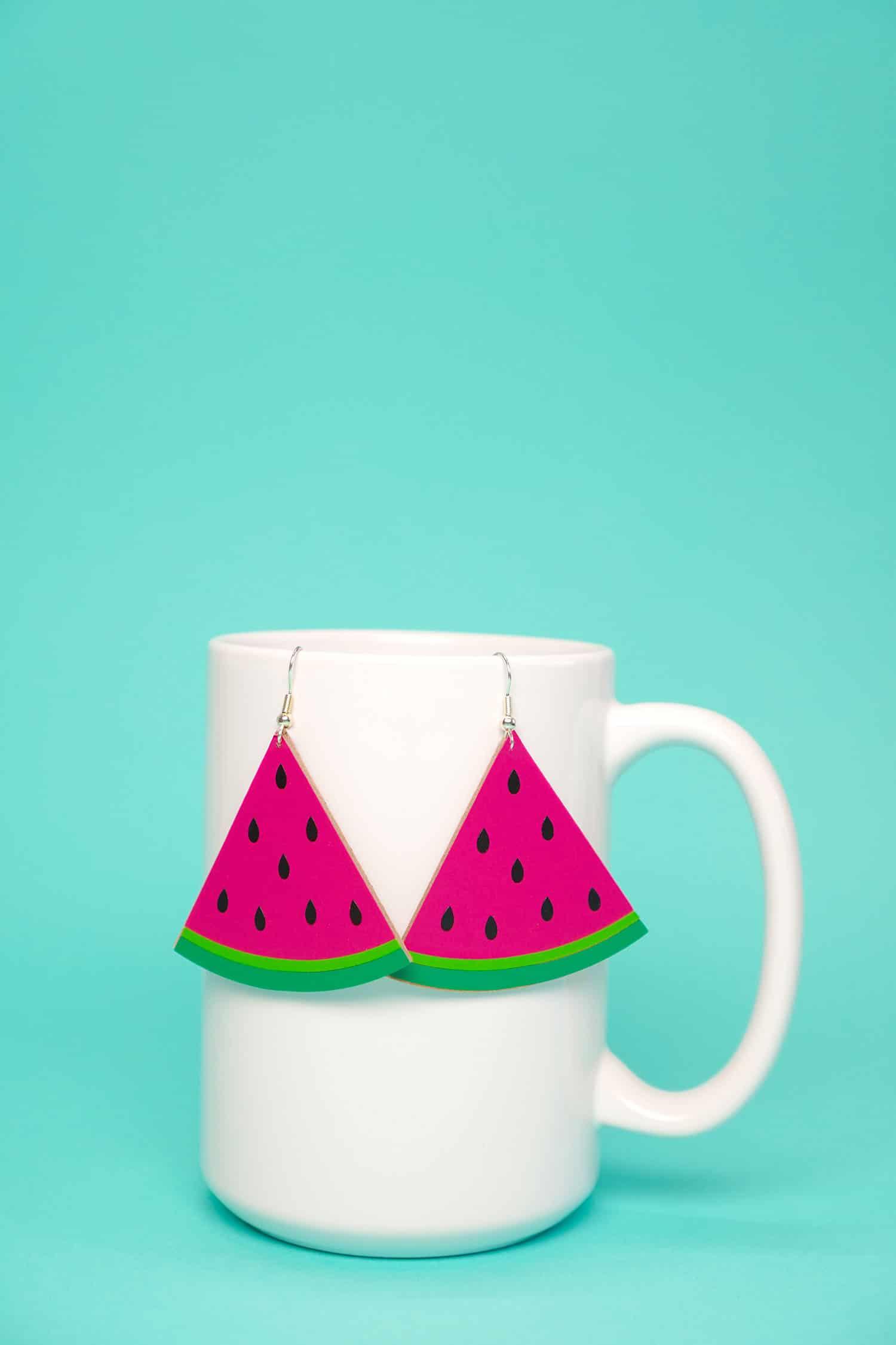 watermelon shaped earrings hanging on a white mug