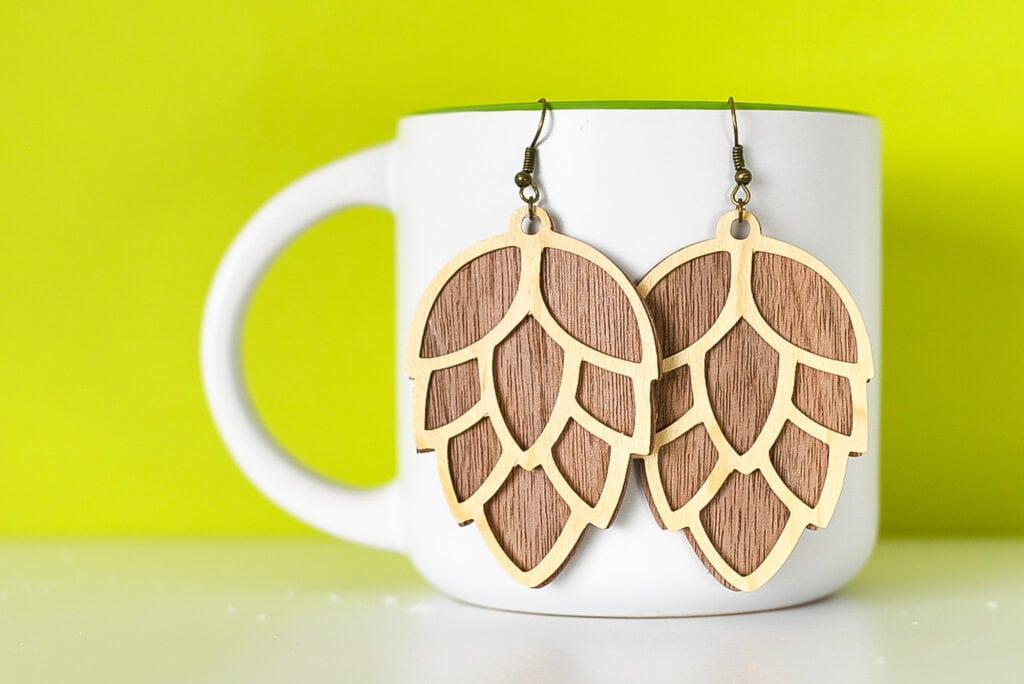 pinecone earrings made from wood veneer hanging on a white mug