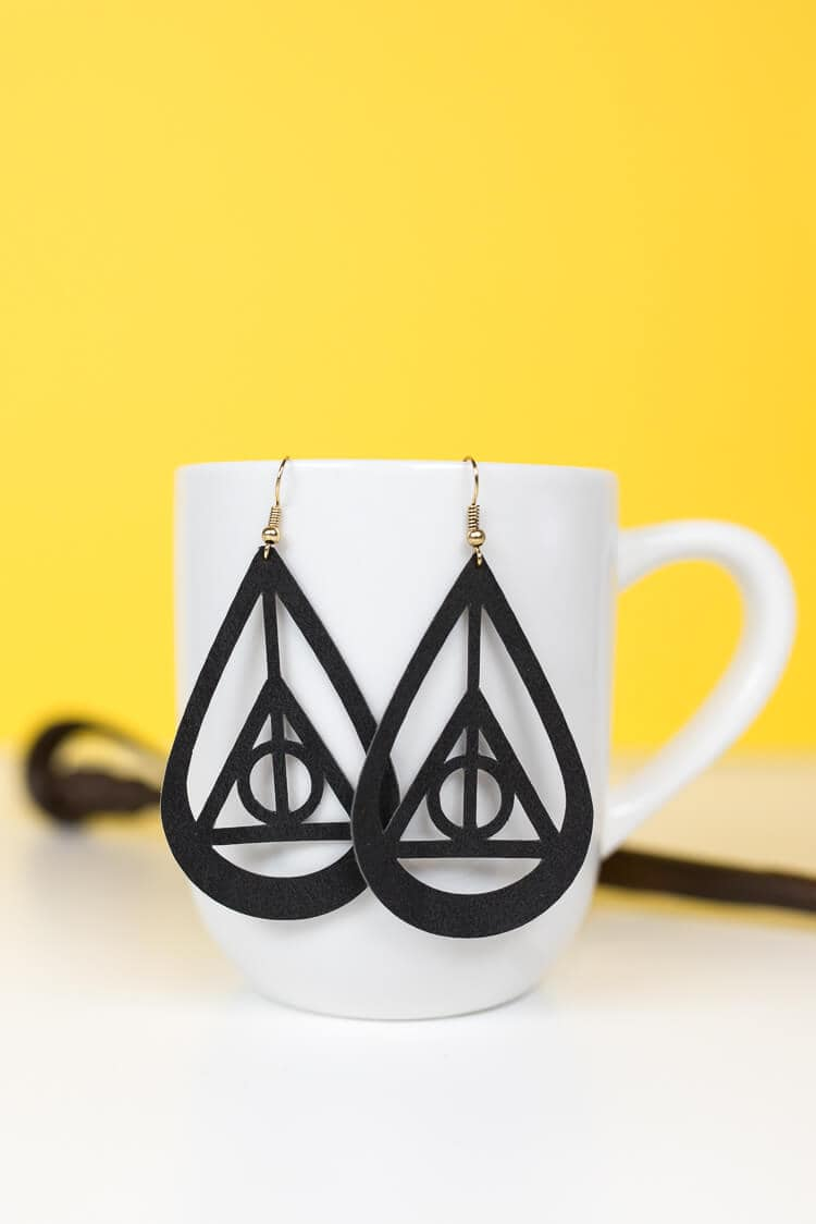 Harry Potter Deathly Hallows earrings hanging on a white mug